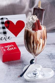 Красивая миска ванильного мороженого с шоколадным эскимо и клубничными фруктами сверху. в красной рамке на португальском написано