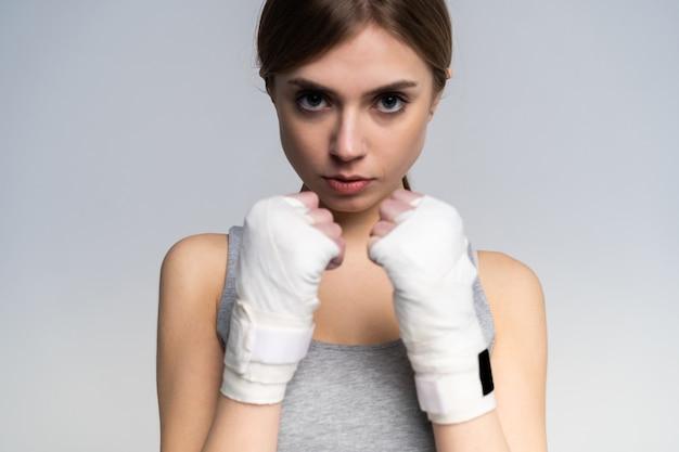 회색 위에 스튜디오에서 연습하는 낚시를 좋아하는 의류와 장갑을 착용하는 아름 다운 복서 소녀.