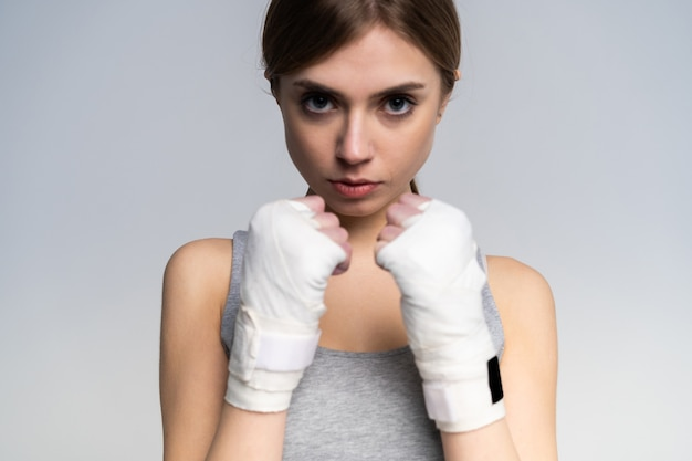 Beautiful boxer girl wearing sportive clothing and gloves practicing in the studio over gray.