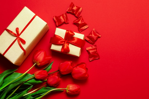 Beautiful boxes wrapped in paper and red ribbon, tulips flowers and candies