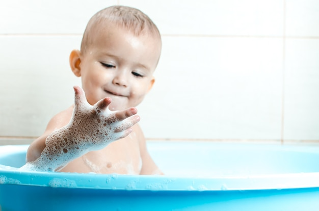 Красивый мальчик купает малыша в ванной чистой и гигиеничной, смотрит на руку, которая в пене
