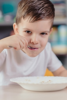 Beautiful boy eats milk porridge. cute baby having breakfast sitting at a table in the kitchen at home.