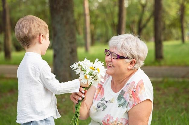 おばあちゃんに花を与える美しい少年。母の日おめでとう。