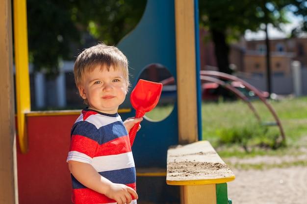 모래 상자에 있는 아름다운 소년은 빨간 삽을 가지고 노는다