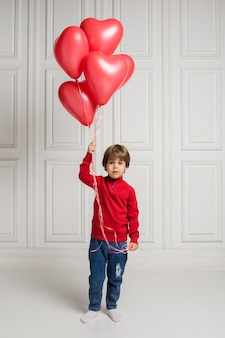 Beautiful boy in jeans and sweater holding heart balloons on white background