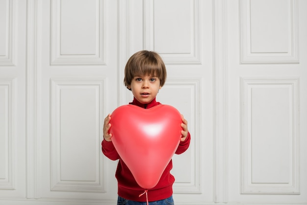 A beautiful boy in jeans and a sweater holds a red heart balloon on a white background with space for text