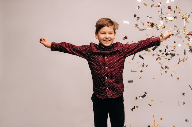 회색 배경에 색종이 조각을 들고 기쁨을 위해 점프하는 아름다운 소년