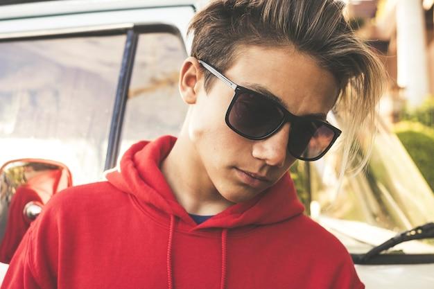 Красивый мальчик модель молодой возраст поза на открытом воздухе с черными солнцезащитными очками и светлыми длинными волосами