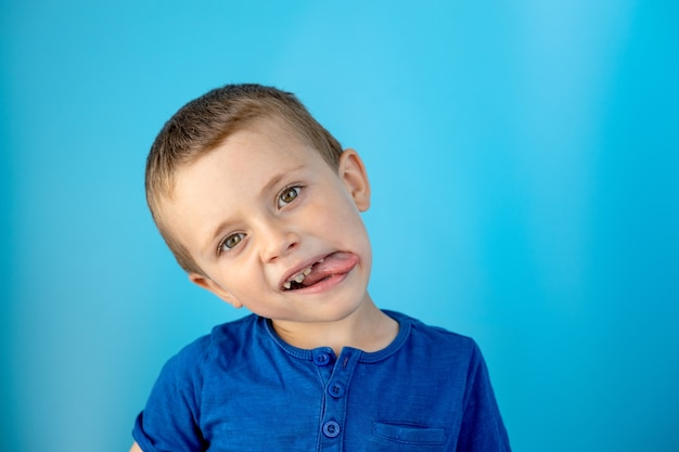 美しい少年は舌を見せて、青い壁の上で楽しんでいます。