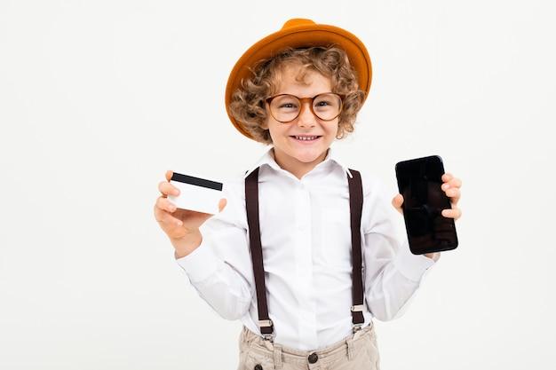 Красивый мальчик с вьющимися волосами в белой рубашке, коричневой шляпе, очках с черными подтяжками показывает телефон и денежную карту на белом фоне