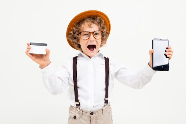 Красивый мальчик с вьющимися волосами в белой рубашке, коричневой шляпе, очках с черными подтяжками показывает телефон и денежную карту на белом