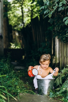 Beautiful boy with white hair and a combination is played with a bucket of water and a mug near the fence