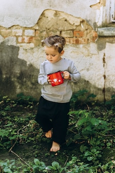 Beautiful boy with a white hair red mug and a bucket next to the old hut