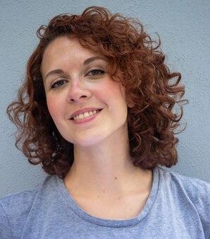 Красивая бразильская рыжая модель улыбается и позирует перед камерой.
