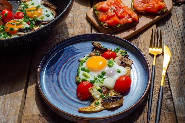 木製のテーブルの美しい朝食。キノコとネギの目玉焼き