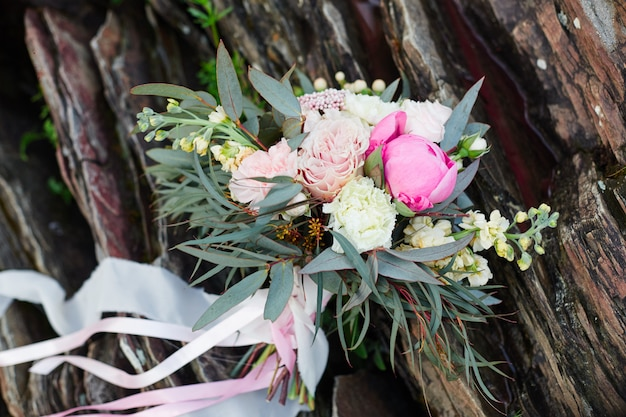 Beautiful bridal bouquet lying on the stones