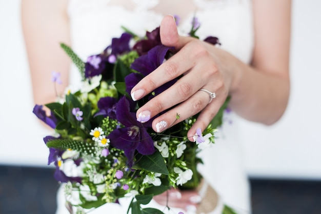 Beautiful bridal bouquet with different colors and hand with ring