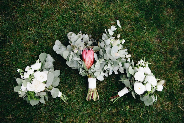 Beautiful bridal and bridesmaids bouquets isolated on grass