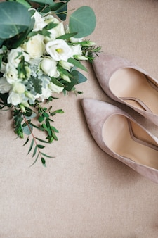 Beautiful bridal shoes are standing next to a bouquet of flowers