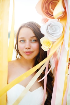 Beautiful bride among paper flowers decoration