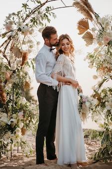 ビーチでの結婚式をしている美しい新郎新婦