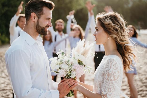 ビーチでゲストと結婚式をする美しい新郎新婦