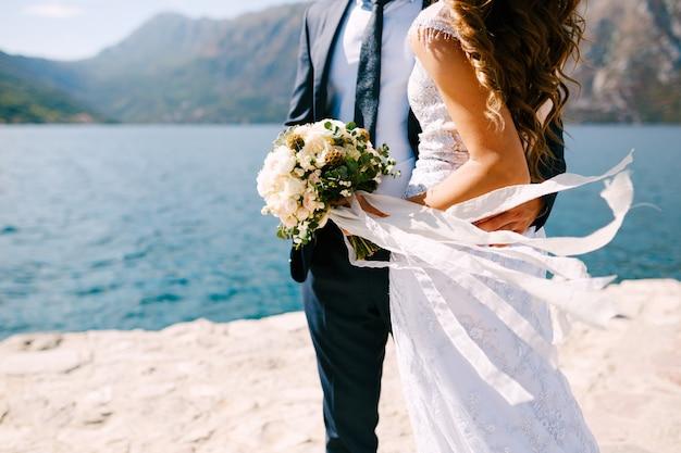 Красивая невеста и жених обнимаются на берегу, невеста держит букет цветов