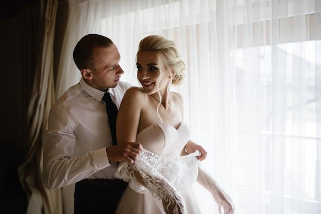 Красивая невеста и жених в гостиничном номере