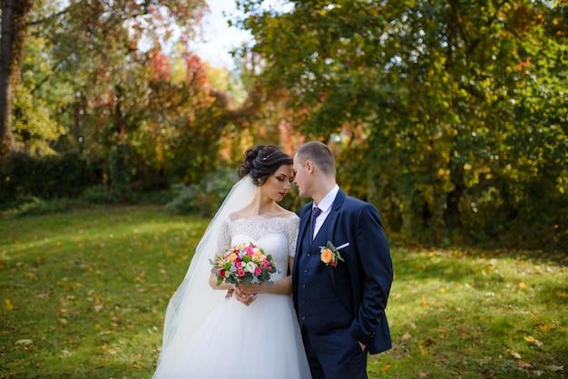 Красивая невеста и жених в зеленом парке
