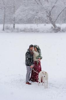白い犬と一緒に美しい新郎新婦が雪に覆われた森の背景に立っています。