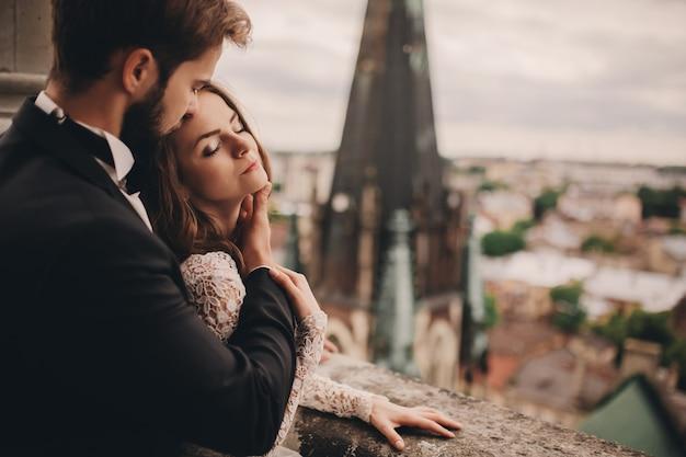 아름다운 신부와 세련된 신랑은 탁 트인 도시 전망이있는 오래된 고딕 양식의 대성당 발코니에서 포옹하고 있습니다.