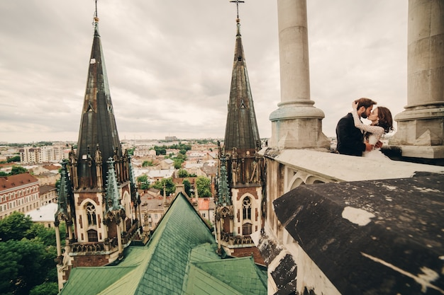 아름다운 신부와 세련된 신랑은 탁 트인 도시 전망이있는 오래된 고딕 성당의 발코니에서 키스하고 있습니다.
