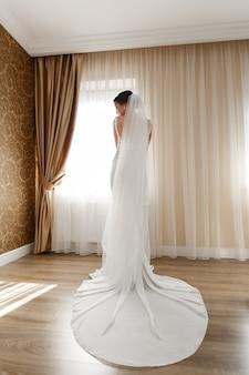 Beautiful bride in chic long dress indoor in hotel room