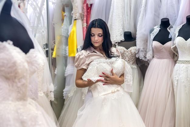Beautiful bride choosing dress for her wedding