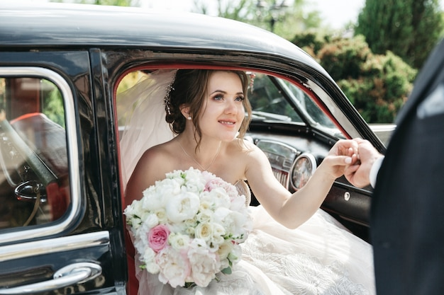 The beautiful bride comes out of the car