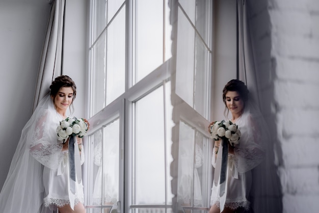 Beautiful bride dressed in silk nightwear and veil is holding wedding bouquet made of white peonies near the huge window