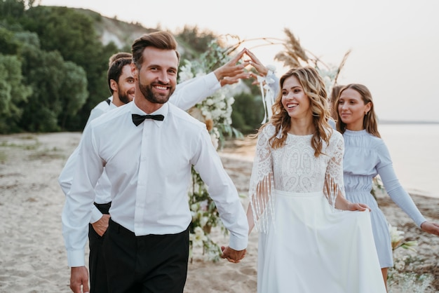 Beautiful bride and groom having their wedding with guests on a beach