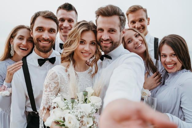 Bellissimi sposi che festeggiano il loro matrimonio con gli ospiti su una spiaggia