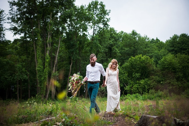 Beautiful bride and groom hipster stand on forest, rustic style