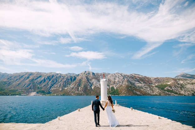 Beautiful bride and groom holding hands walk along the pier on a sunny summer day