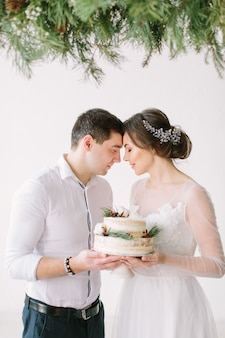 Beautiful bride and groom look at each other at the table in the banquet hall and holding wedding cake decorated with berries and cotton