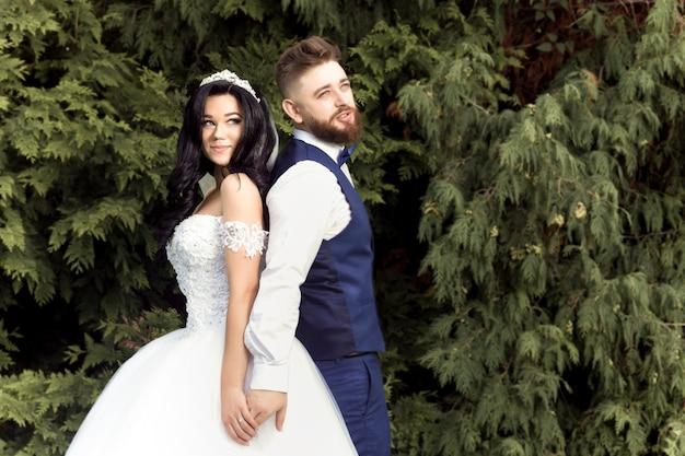 Beautiful bride and groom in wedding dresses posing in camera