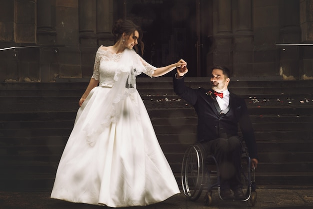Beautiful bride and groom on the wheelchair dance before old catholic church