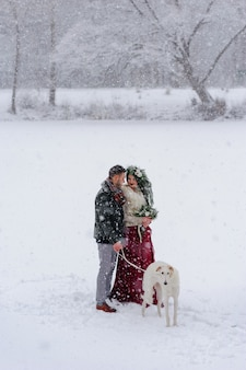 Beautiful bride and groom with a white dog are standing on the background of a snowy forest