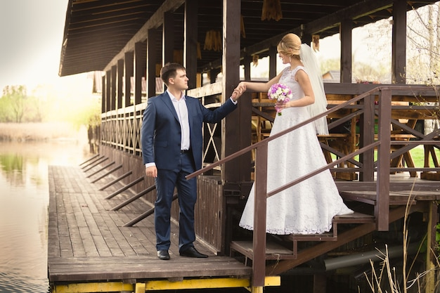 Beautiful bride and handsome groom walking down the stairs on pier