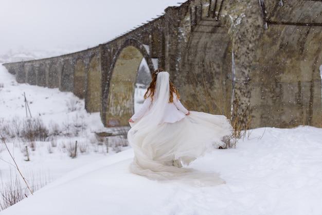 Beautiful bride in her wedding dress in the winter