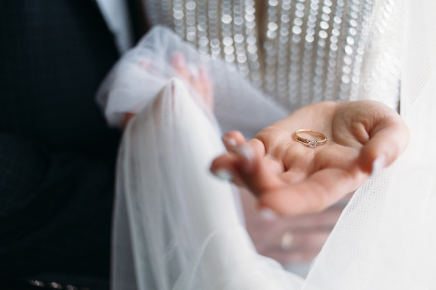 The beautiful bride holds a wedding ring
