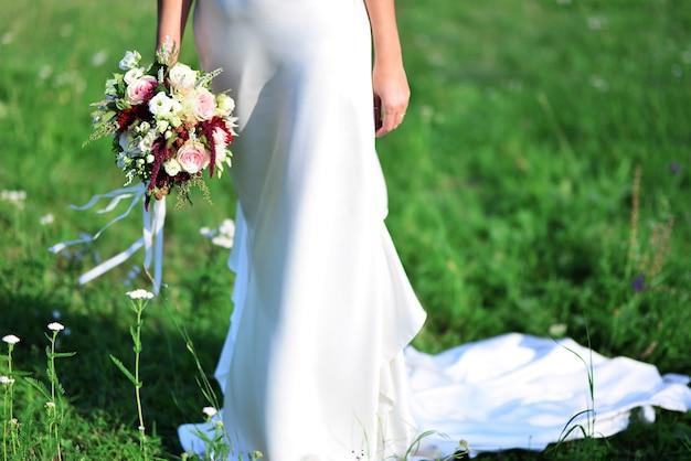 에코 스타일의 고급스러운 드레스에 아름다운 신부. 꽃다발을 들고 신부입니다. 결혼식 꽃. 소프트 포커스.