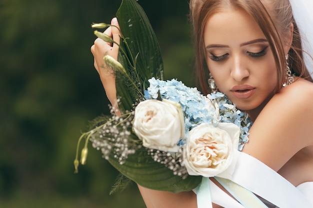 通りの緑の中でポーズをとる壮大なウェディングドレスの美しい花嫁。女の子は広告のためのウェディングドレスでポーズをとる。ドレスを宣伝するための花嫁のコンセプト。