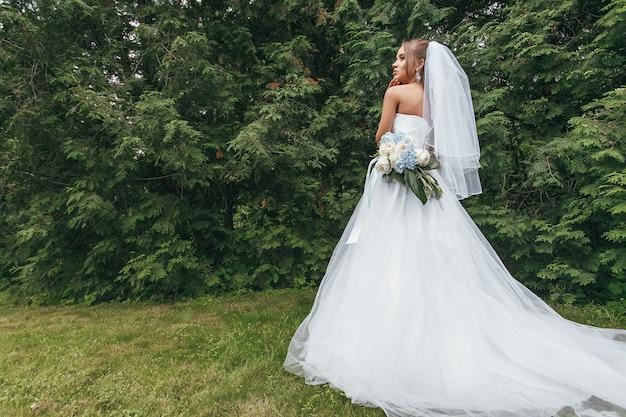 Красивая невеста в пышном свадебном платье позирует среди зелени на улице. женщина позирует в свадебном платье для рекламы. концепция невесты для рекламы платьев
